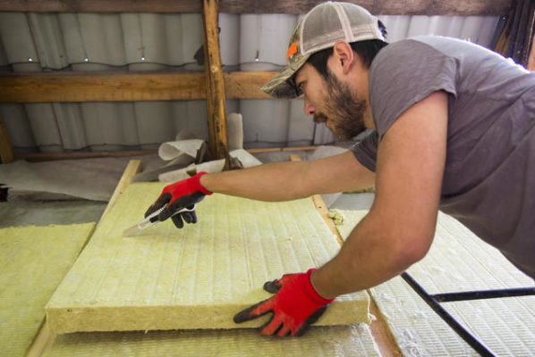Efficiency worker insulating a home